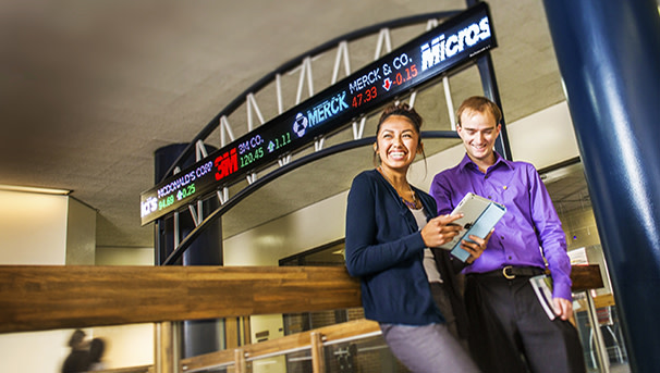 Students in front of stock market ticker
