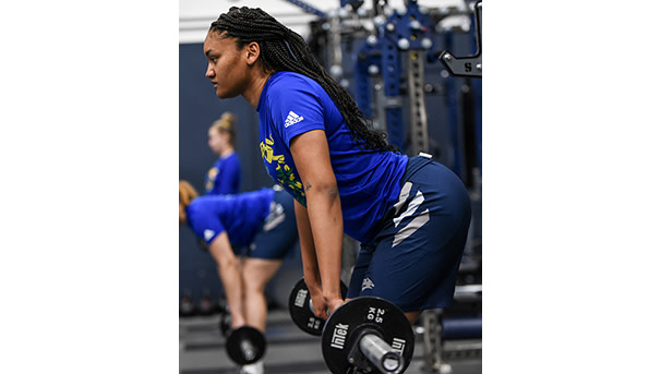 Female student-athlete lifting weights