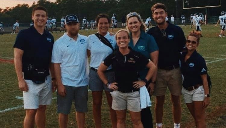 Athletic training student and preceptors at a local high school football game