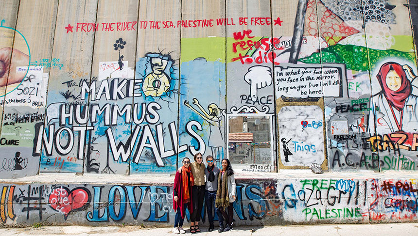 Pal-Trek participants pose near the street-art covered West Bank barrier wall.