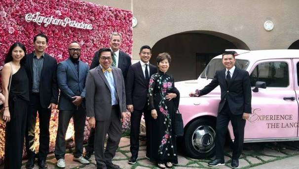 Family Business owners standing outside in front of a pink car