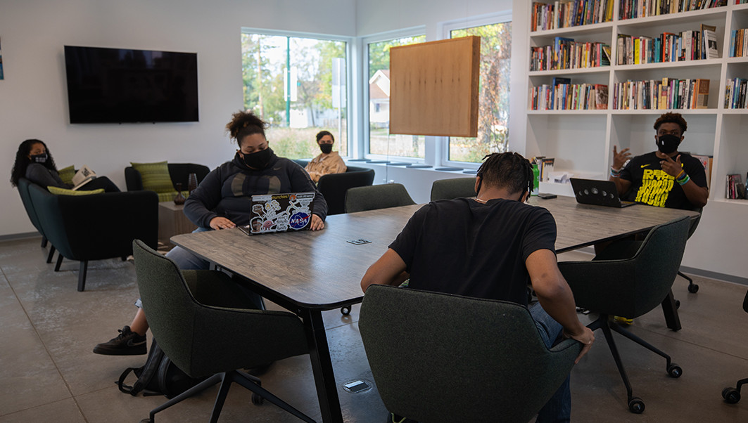 Students wearing masks talk and study at a table at the LRP BCC.