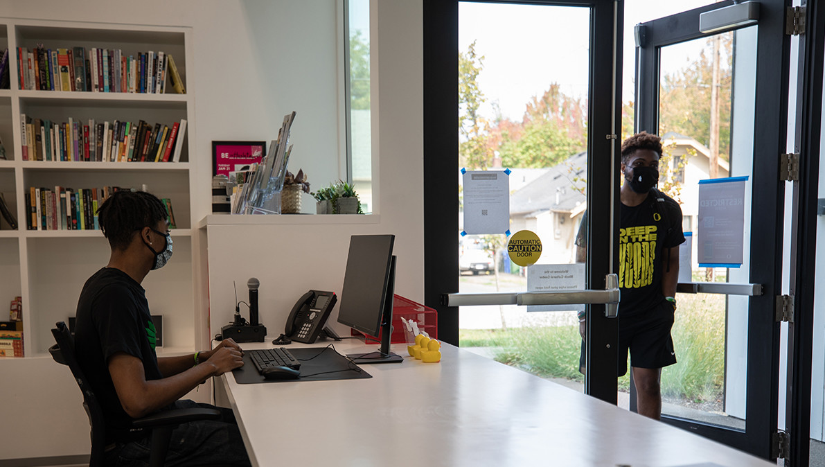 A student wearing a mask walks in the doors of the Lyllye Reynolds-Parker Black Cultural Center.