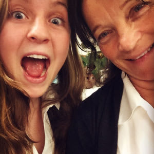 Amanda Semple, pictured with an exaggerated expression of surprise pictured with a smiling person wearing a white dress shirt under a black blazer.
