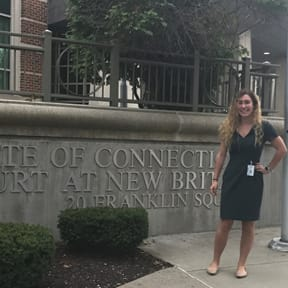 """Gillian Peters stands in front of a wall with """"State of Connecticut, Court at New Britain, 20 franklin Square"""""""