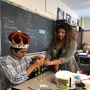 Amber-Nicole Rodriguez assists a student wearing a crown with assembling a model.