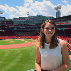 Hannah Pyenson stands in the outfield of a baseball stadium.
