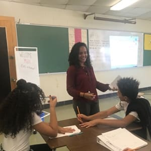 Astrid Esquilin Nieves pictured standing in a classroom in front of two kids