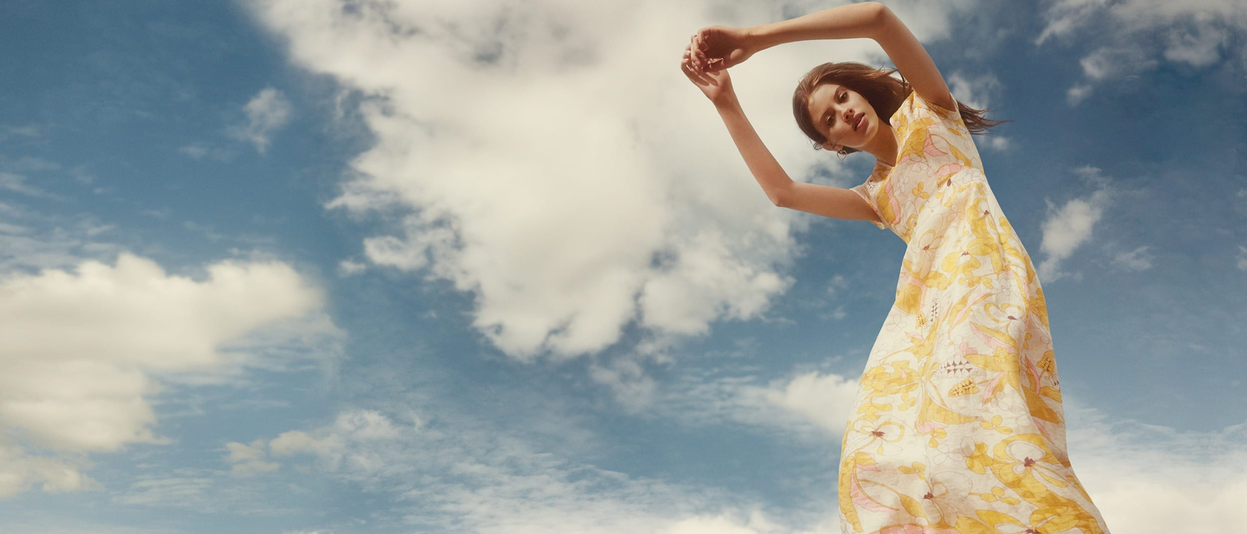 Max & co girl in yellow pink white floral dress with sky and clouds