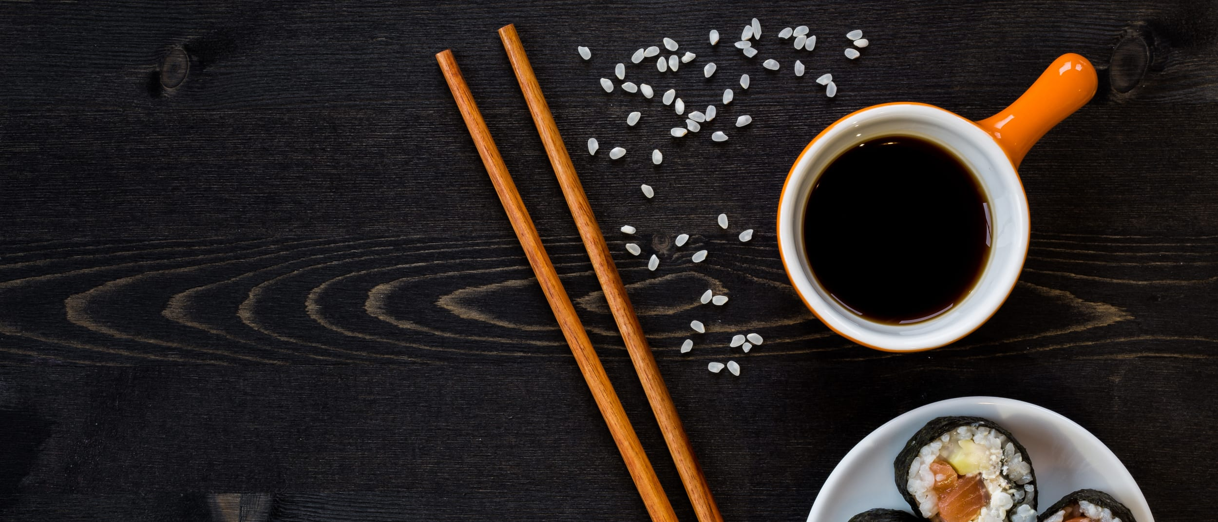 black background with sushi, chopsticks and soy sauce
