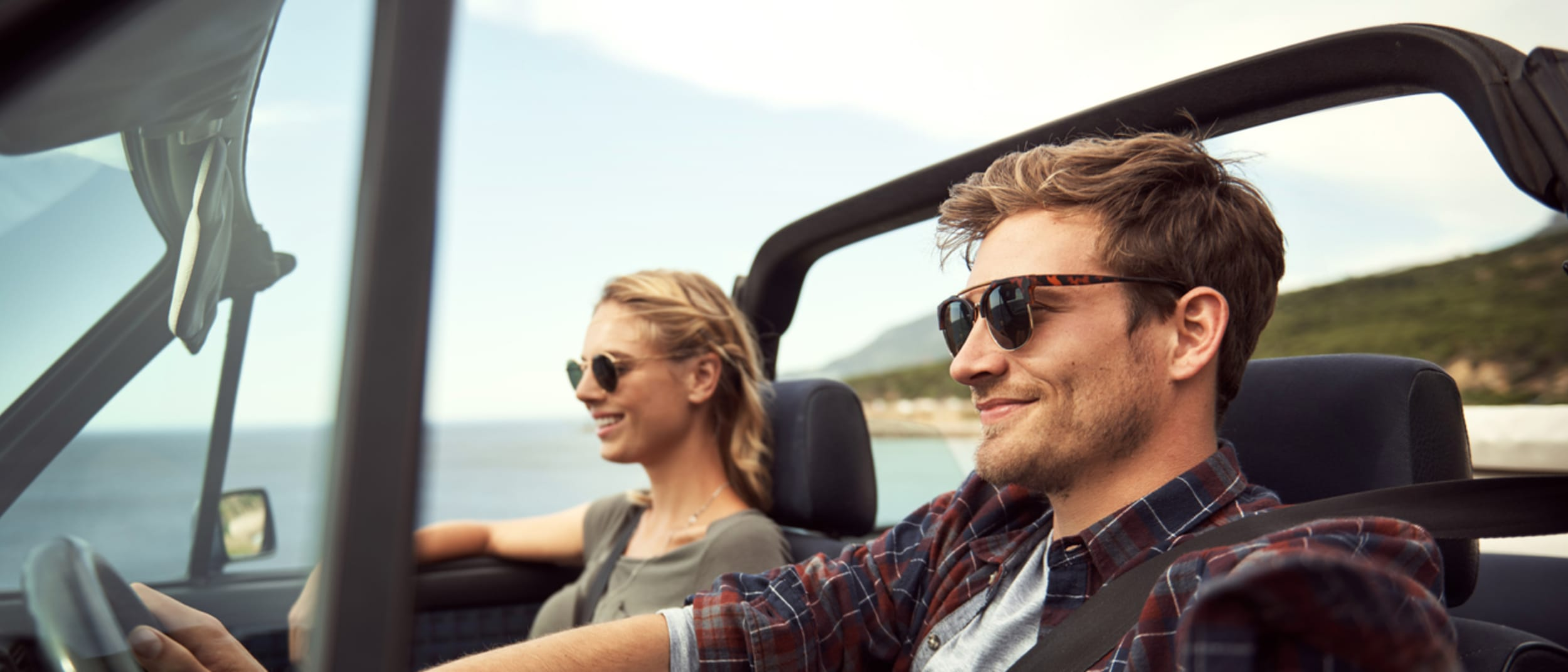 Man and woman driving wearing sunglasses