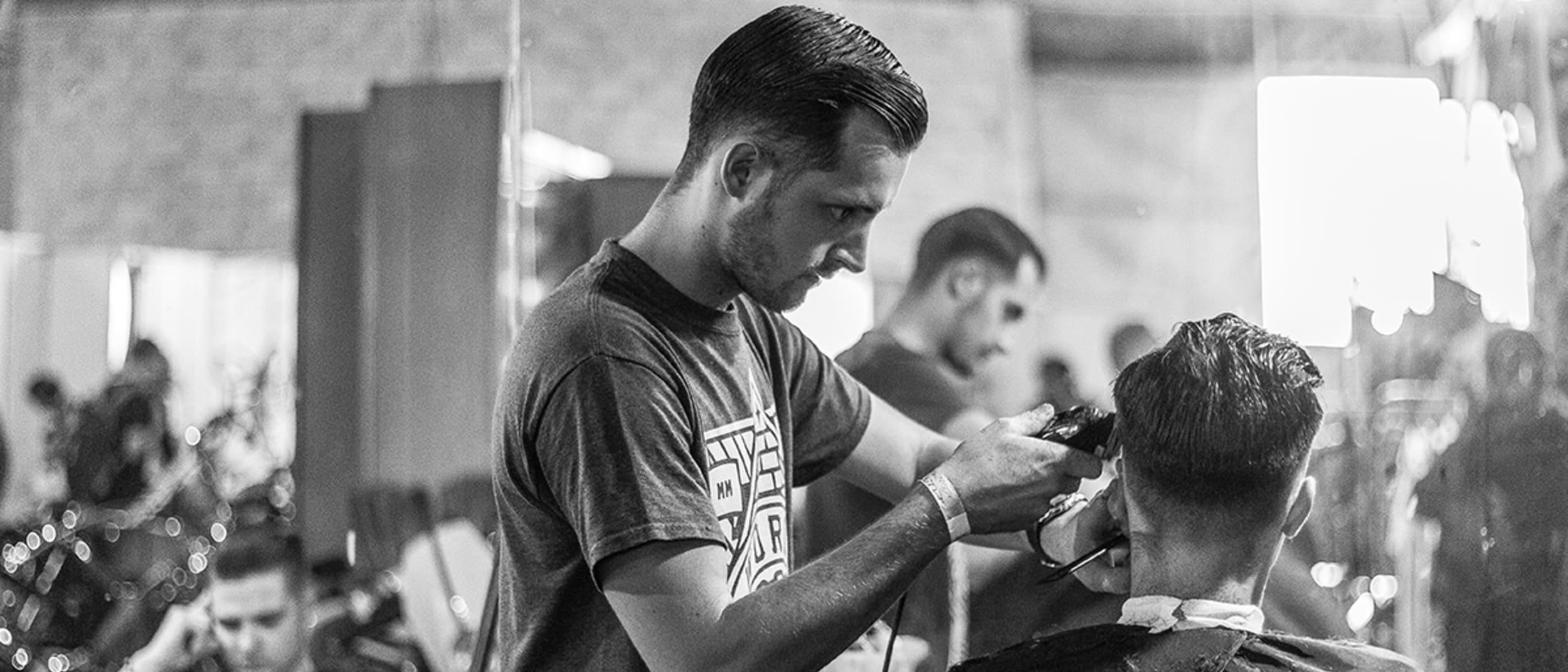 Man getting his hair cut at a barber shop.
