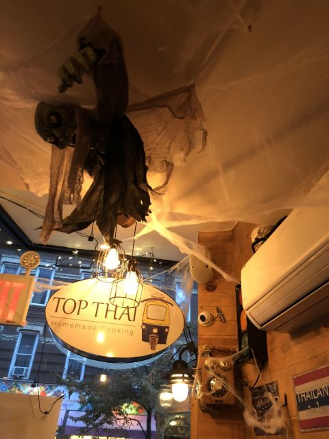 restauarnt interior decorated for Halloween with a ghoul hanging from the ceiling, fake spiderwebs, and a skull atop an air conditioner