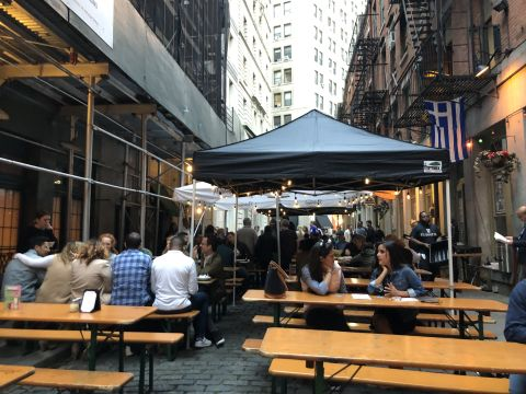 a gray brick street in New York City packed with construction scaffolding and wooden tables, some covered by canopies, a few with people seated at them.