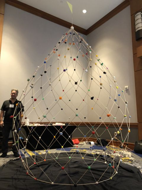 A collection of colorful 3D-printed nodes are connected by wooden rods to form a dome in the shape of a candle flame. Atop it sits a triangular yellow flag. This is the completed Zonodome.