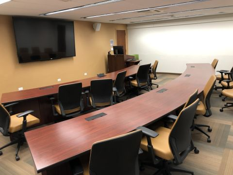 a conference room with two large curved tables facing a large television