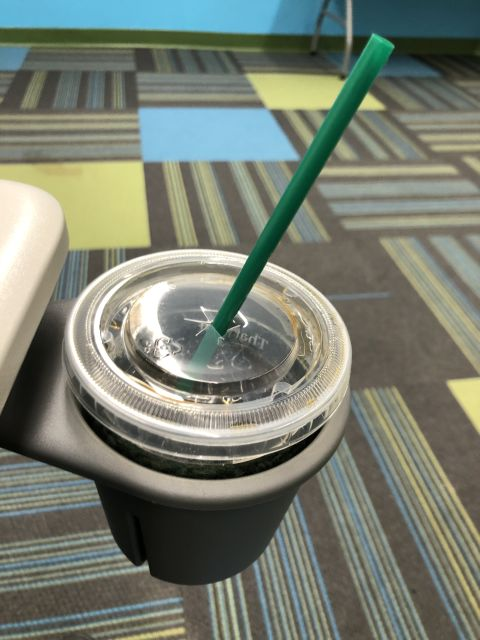 a plastic coffee cup with straw in a cupholder that hangs from a desk