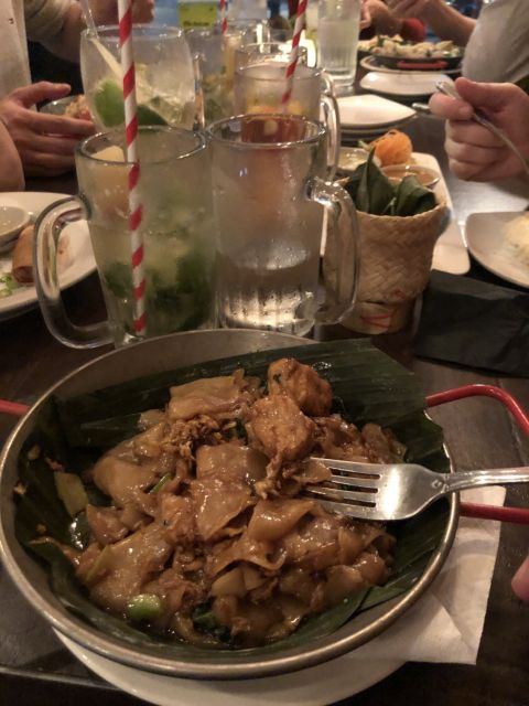 pad see yew with tofu with mugs of drinks in the background