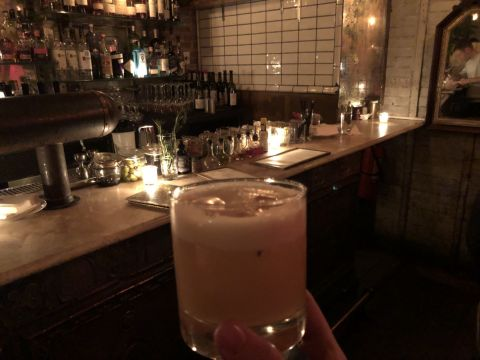 yellow cocktail with foamy head in a lowball glass held in front of a bar containing a very well-organized collection of syrups and bitters