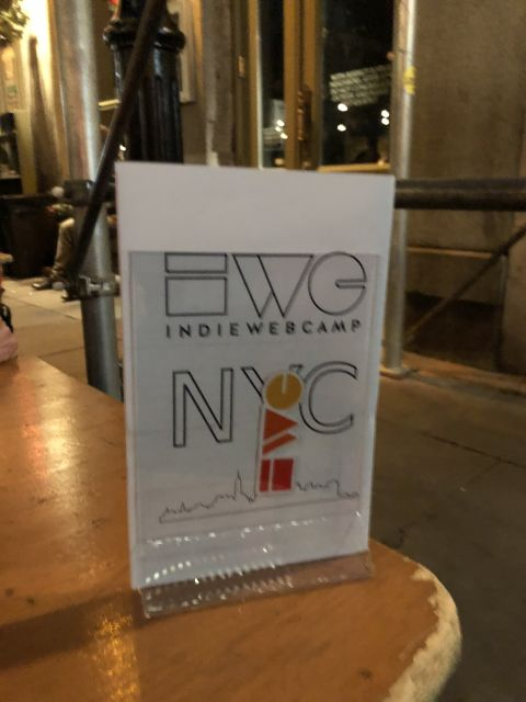 a document stand on a wooden table holds a sign announcing IWC NYC