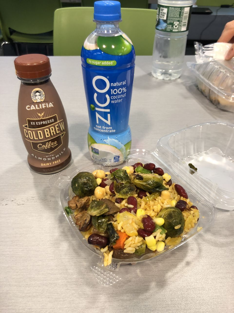 a bottle of cold brew coffee, a bottle of coconut water, and a plastic clamshell full of rice, beans, and brussels sprouts