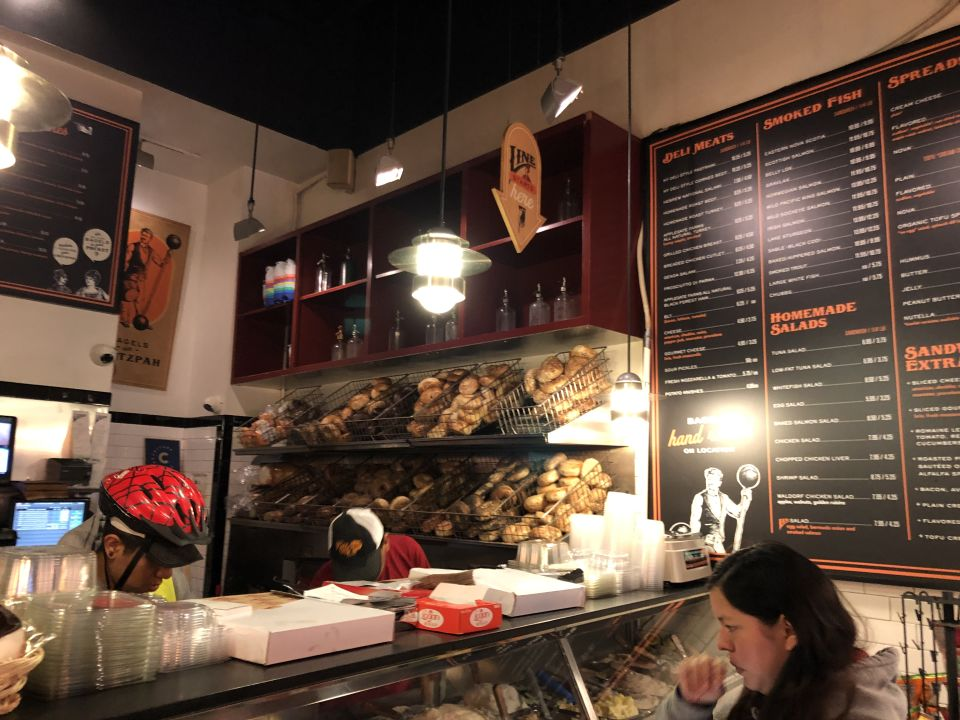 a glass-front deli counter filled with spreads in front of a wall of bagels