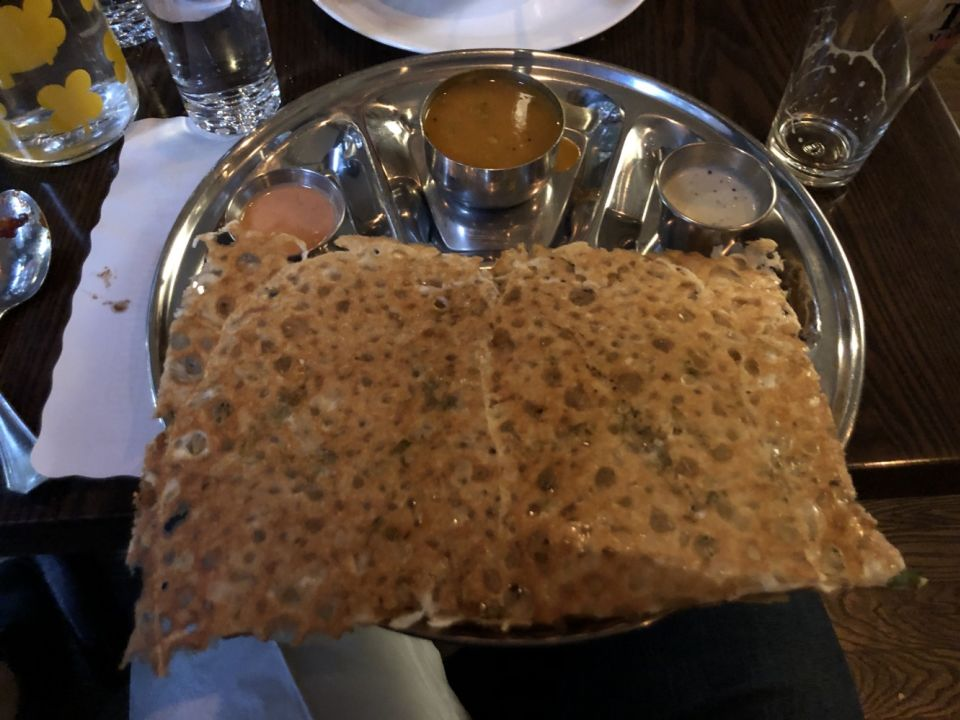 a large dosa on a small circular metal tray