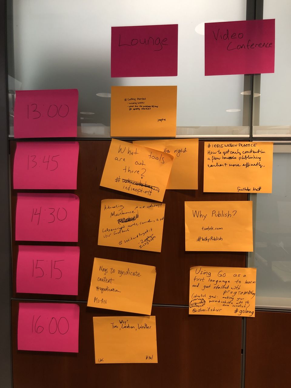 wood and glass cubicle wall covered in pink and orange sticky notes indicating times, rooms, and topics to discuss