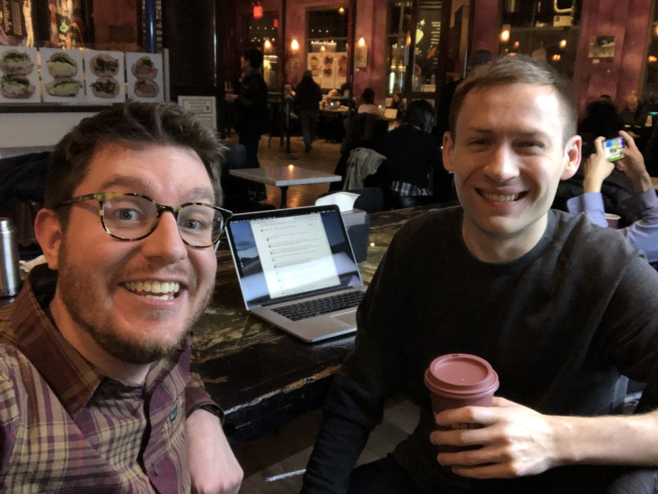 Marty and Dmitri smile at the camera. Behind them coffee shop patrons go about their business.
