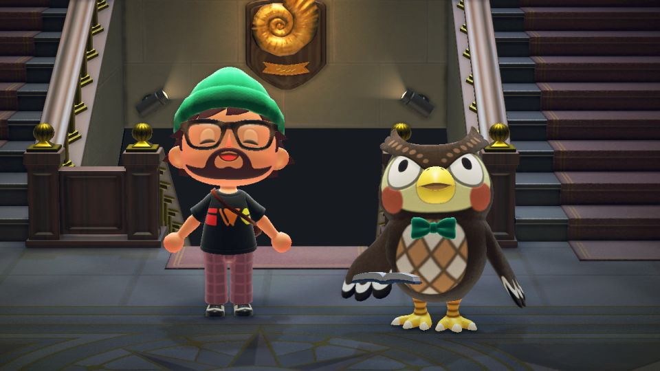 Marty's character in Animal Crossing wearing an IndieWebCamp t-shirt smiles while standing next to Blathers the owl.