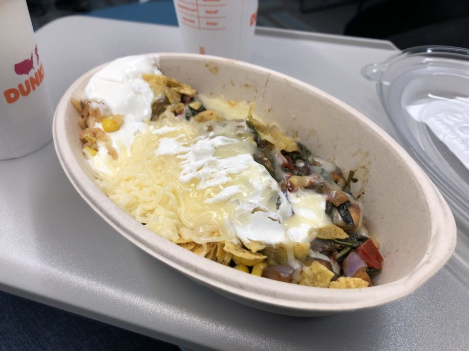 a cardboard container filled with beans, rice, vegetables, cheese, and sour cream