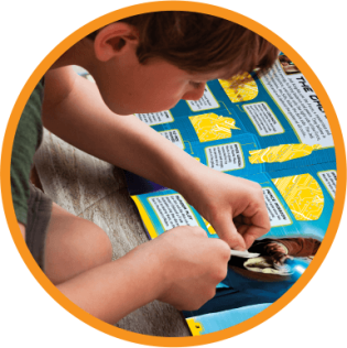 boy placing a sticker on an activity book