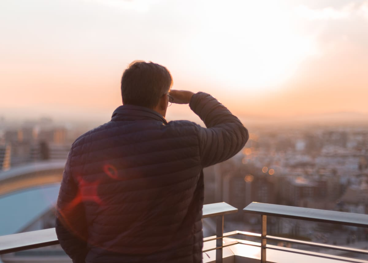 man watching rooftop sunset