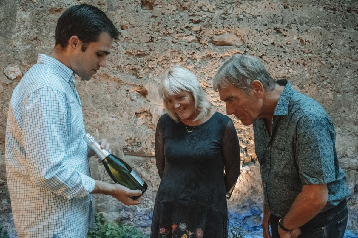 Host explaining wines to couple
