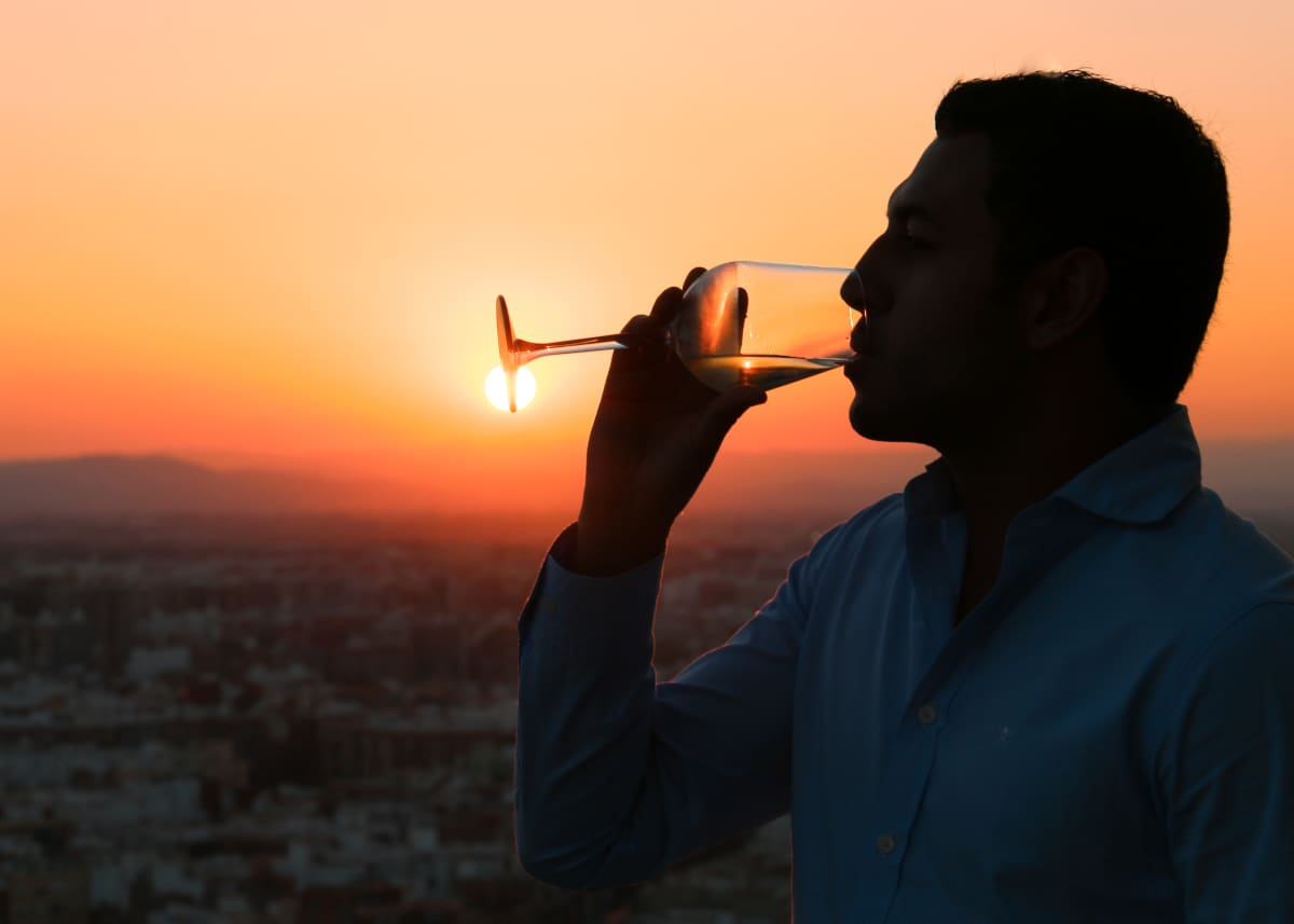 man drinking wine at sunset
