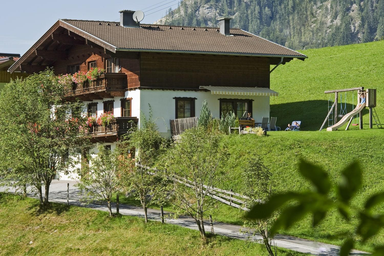 Unser Ferienhaus im Sommer mit Sonnenterrasse gleich am Haus. Am Spielplatz, Grillplatz u. Liegewiese kann man richtig entspanne!
