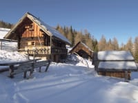 Außenansicht der Hütte mit altem Stall im Winter