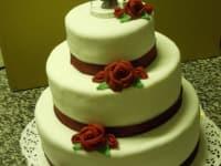 Hochzeitstorte mit roten Rosen und Band