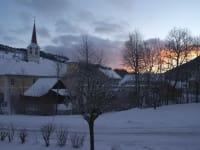 Sonnenuntergang im verschneiten Dorf