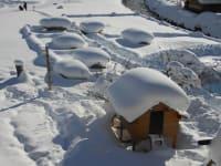 Blick vom Balkon auf den verschneiten Spielplatz
