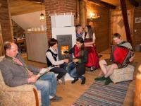 Aufenthaltraum im Zirbenlandappartment mit Kamin und TV , offener Wohnbereich zur Wohnküche