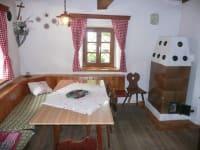 Wohnstube mit Esstisch und Kachelofen