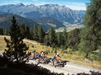Mountain bikers with a view of Nauders and the Samnaun group.
