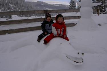 Kinder auf dem Schneekroko vor der Hütte