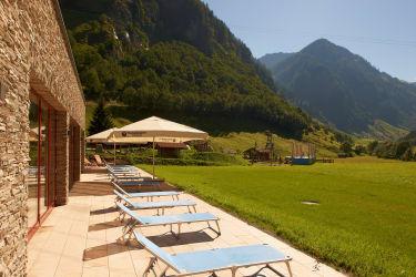 Hallenbad mit Liegewiese und Blick auf Spielplatz und Bergwelt