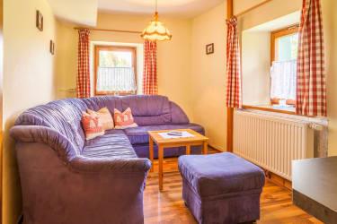 Wohnzimmer mit gemütlicher Couch und Sat/TV