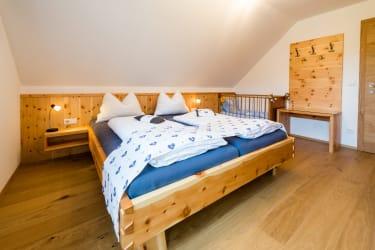 blaues Zirbenschlafzimmer mit Gitterbett