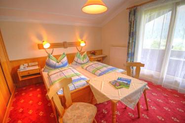 geräumiges Vollholz-Zimmer mit Sofa, Teppichboden und Fernblick