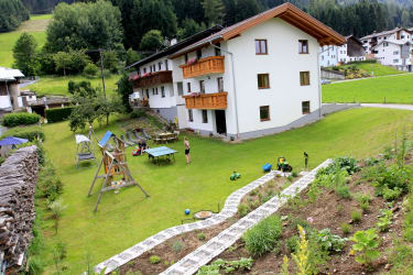große Spiel- und Liegewiese hinter dem Haus mit Kräutergarten