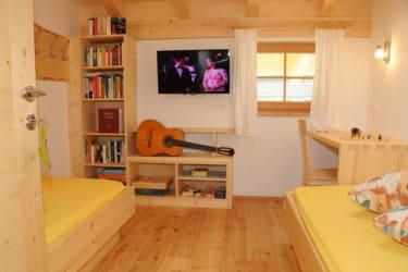 TV-Zimmer mit bequemen Liegen, Bücher, Spiele für den Familienabend, FeWo Dolomitenblick